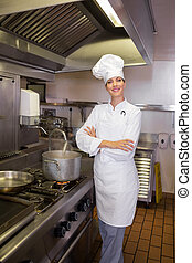 Smiling female cook with arms crossed in kitchen