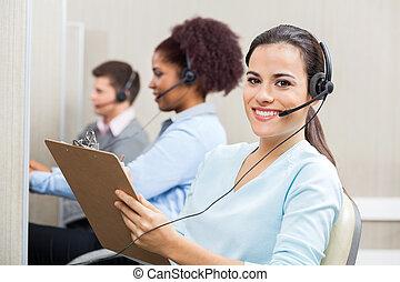 Smiling Female Customer Service Representative Writing On...
