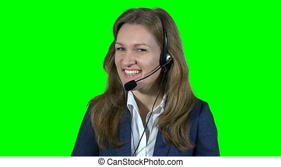 Smiling female customer support operator consultant with headset consulting customer online. Green background. Static closeup shot. 4K UHD