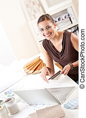 Smiling female designer with color swatch and laptop at ...