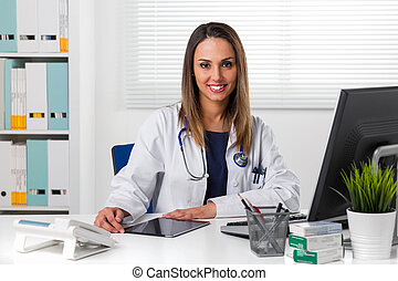 Smiling female doctor at desk using tablet