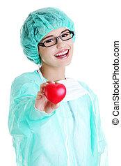 Smiling female doctor or nurse holding heart