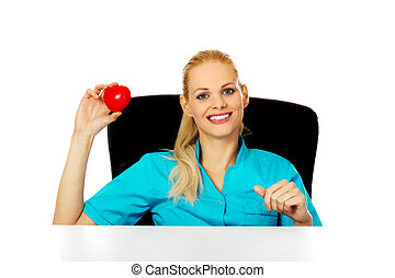 Smiling female doctor or nurse sitting behind the desk and holding heart toy