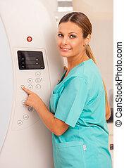 Smiling female doctor setting up mri machine