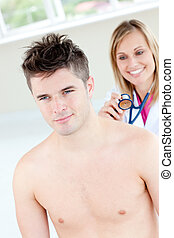 Smiling female doctor sounding her male patient