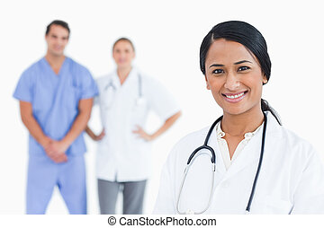 Smiling female doctor with colleagues behind her