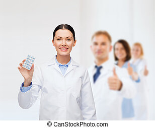 smiling female doctor with pills - healthcare, medicine and...
