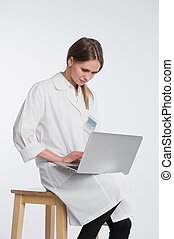 Smiling female doctor working on her laptop against a white background