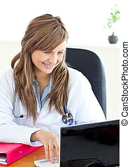 Smiling female doctor working with a laptop