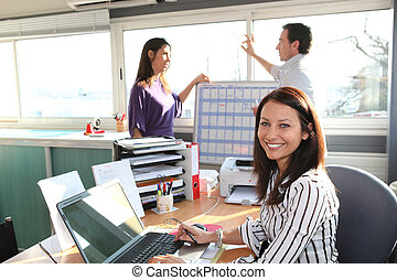 smiling female employee in office and colleagues in ...