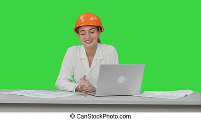 Smiling female engineer talking to the camera sitting on the desk with a lot of papers on a Green Screen, Chroma Key.