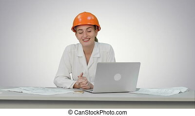 Smiling female engineer talking to the camera sitting on the desk with a lot of papers on white background.