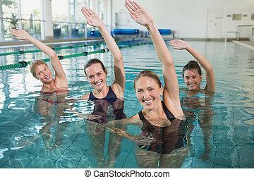 Smiling female fitness class doing aqua aerobics in swimming...