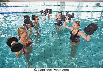 Smiling female fitness class doing aqua aerobics with foam ...