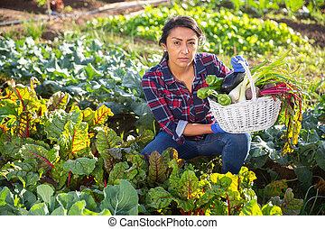 Smiling female gardener holding vegetables grown in home garden