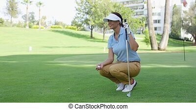 Smiling female golfer with brown hair crouches with club and...