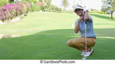 Smiling female golfer with brown hair crouches