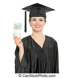 Smiling female graduation student showing pack of euros. HQ photo. Not oversharpened. Not oversaturated