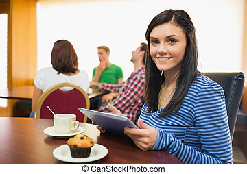 Smiling female having breakfast while using tablet PC with students around table in background at  the coffee shop