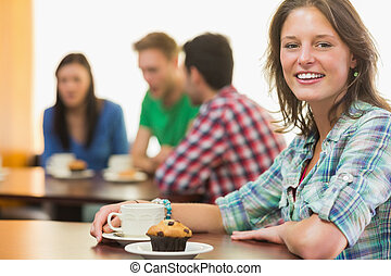 Smiling female having coffee and muffin at  coffee shop