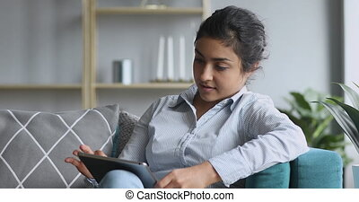 Happy indian millennial girl sitting on comfy sofa, using digital tablet, satisfied with remote work results. Smiling female hindu customer shopping online in internet store, web surfing information.