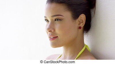 Smiling female in bikini top near blank wall