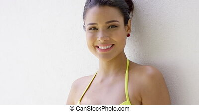Smiling female in bikini top near blank wall - Single...