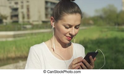 Smiling female in headphones with smartphone