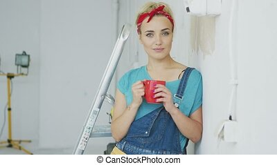 Smiling female in overalls leaning on wall - Beautiful blond...
