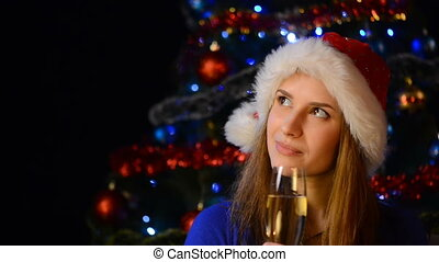 Smiling female in Santa hat with glass of champagne looking...