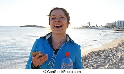 Smiling Female Jogger at Sunset on the beach - Smiling...