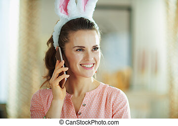 smiling female looking into distance and talking on phone