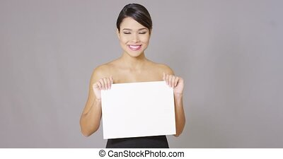 Smiling female looking over at white card in hand