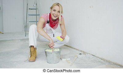 Smiling female mixing yellow wall paint - Happy young blond...
