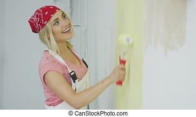 Smiling female painting wall with roller - Side view of...