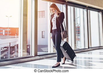 Smiling female passenger proceeding to exit gate pulling suitcase through airport concourse while talking on the phone.