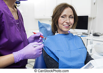 Smiling Female Patient By Dentist Holding Tools - Portrait...