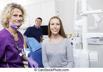 Smiling Female Patient With Dentists In Clinic