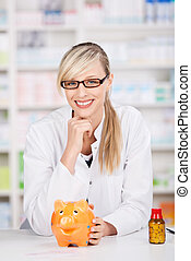 Smiling female pharmacist poses with a piggy-bank