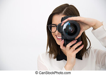 Smiling female photographer with camera over gray background