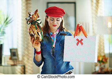smiling female showing easter egg and shopping bag