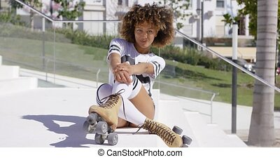 Smiling female sitting on stairs wearing rollerskates