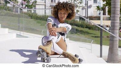 Smiling female sitting on stairs wearing rollerskates