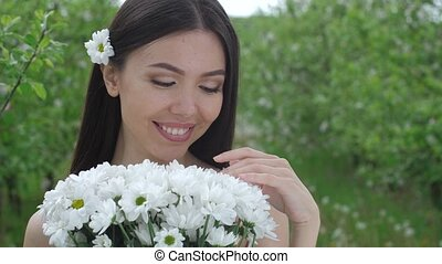 Smiling female sniffing bouquet of flowers outdoor