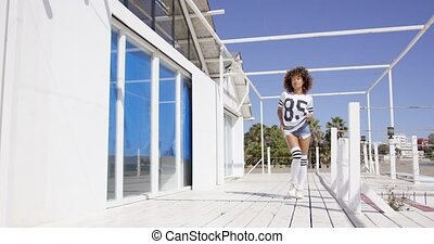 Smiling female standing near white building