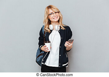 Smiling female student holding cup of coffee and  smartphone