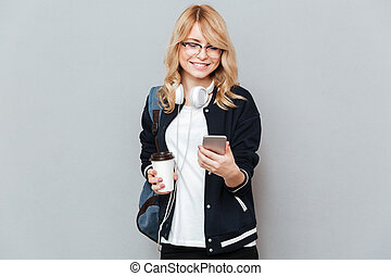 Smiling female student holding cup of coffee and using smartphone