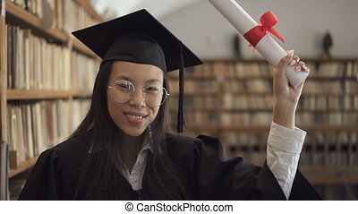Smiling female student in academic gown is posing positively standing in library.