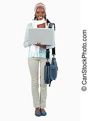 Smiling female student in winter clothing and laptop