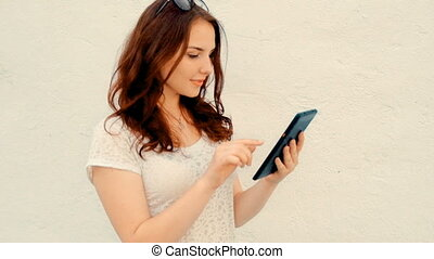 Smiling female student standing in front of wall with digital tablet and looking at screen
